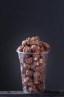 Изысканный сладкий попкорн в пластиковой чашке. шоколадный аромат.