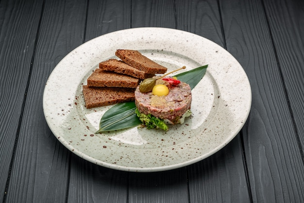 Gourmet tartar raw from beef fillet with yellow of the egg grilled and baguette