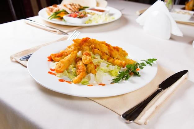 테이블에 제공되는 흰색 둥근 접시에 허브와 야채를 곁들인 맛있는 튀긴 생선 고기.