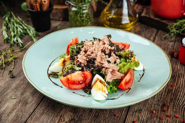 Изысканный салат из тунца с яйцом, зеленью и соусом