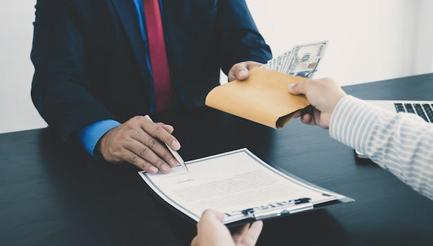 정부 관계자들이 계약서에 서명하고 사업가로부터 뇌물을 받고 있다
