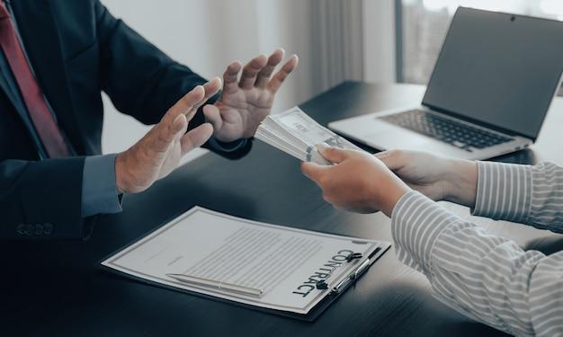 정부 관리들은 부패와 뇌물수수 방지의 개념으로 사업가로부터 뇌물을 받기 위해 돈을 거부하는 손을 들어 올립니다.