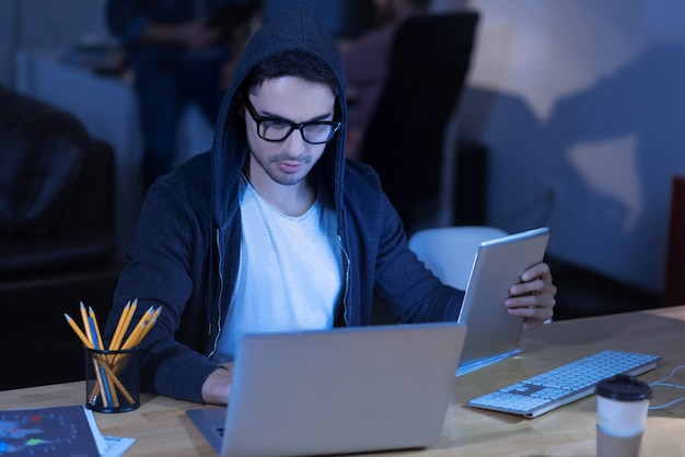 Government secrets. serious smart intelligent man holding a tablet and looking at the laptop screen while hacking into the government security system