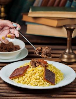 スプーンで伝統的なgovurma plovを食べる女性。