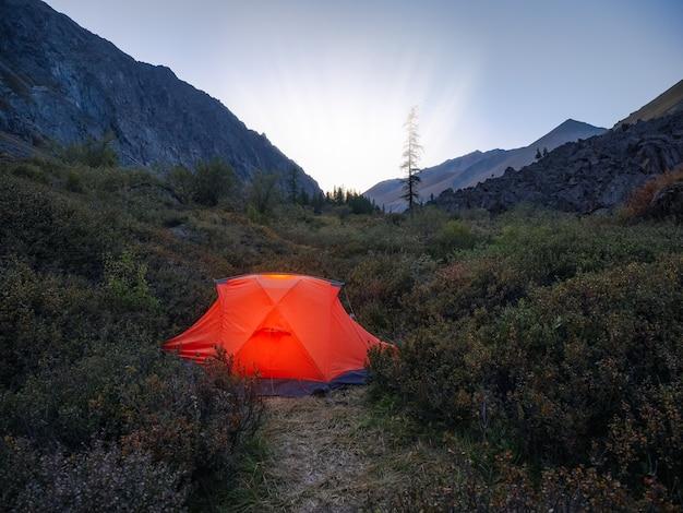 Оранжевый шатер в сумерках в горах. уютный кемпинг в прохладных осенних горах.
