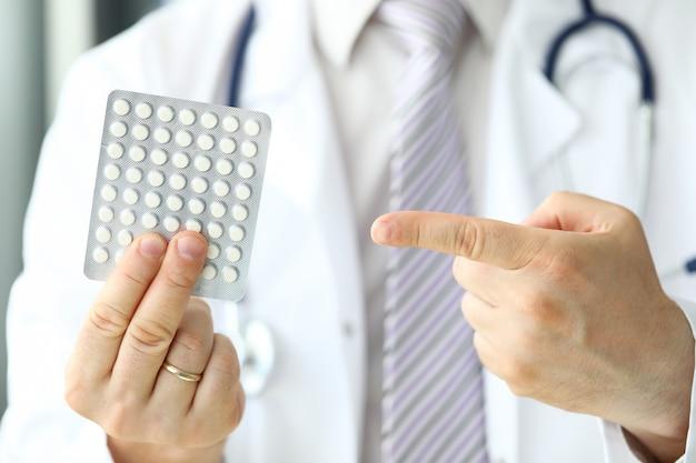 Gp pointing finger at blister full of white tablets