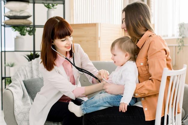 病院または自宅で母親の手で泣いている病気の子供女の赤ちゃん、および検査を持つ女性のgp医師