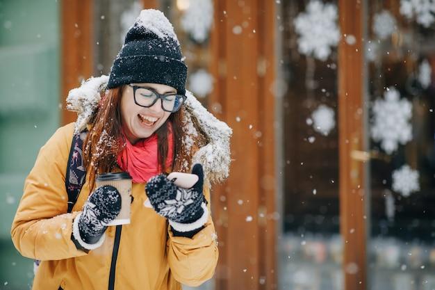 Привлекательная женщина с ее рюкзаком с помощью мобильного телефона. женщина в модном наряде гуляет по зимнему городу, проезжает мимо местных кафе, отправляет смс по телефону, просматривает интернет. используя онлайн карту, gps