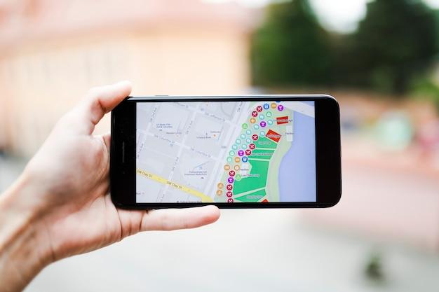 スクリーン上のマップgpsナビゲーションでスマートフォンを持っているツーリスト