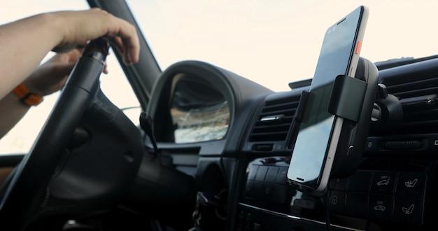 Gps用のダッシュボードに取り付けられたスマートフォンでステアリングホイールに手を繋いでいる車を運転している人