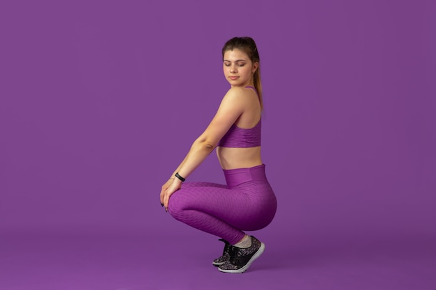 Грейс. красивая молодая спортсменка, практикующая в студии, монохромный фиолетовый портрет.