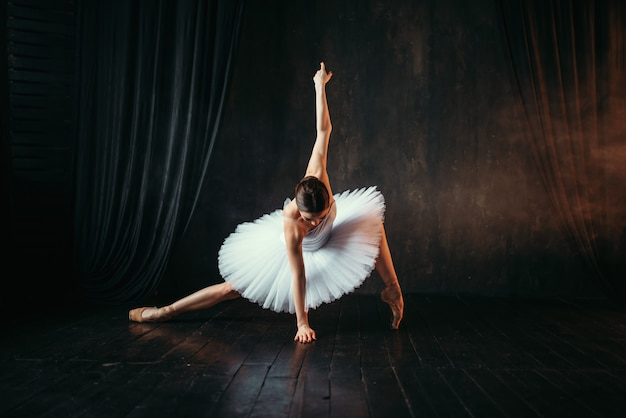 Изящество балерины в белом платье в движении на театральной сцене.