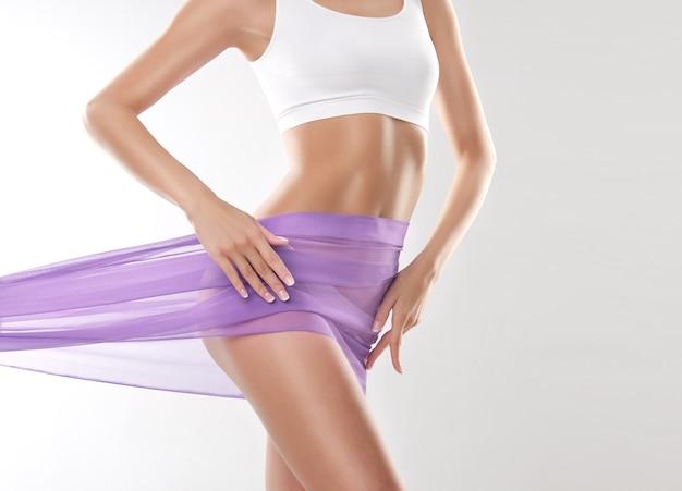 Изящество женского тела женщина, одетая в белый спортивный бюстгальтер и нежный шелк, покрывающий бедра, стройная фигура.