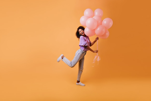 Graceful african female model in casual clothes fooling around on yellow. emotional birthday girl dancing with party balloons.
