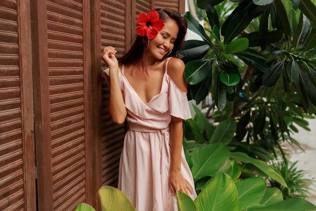 木製の壁でポーズの毛でハイビスカスの花を持つ優雅なアジアの女性。