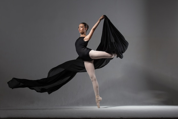 Graceful ballerina in black tights posing with black clothes