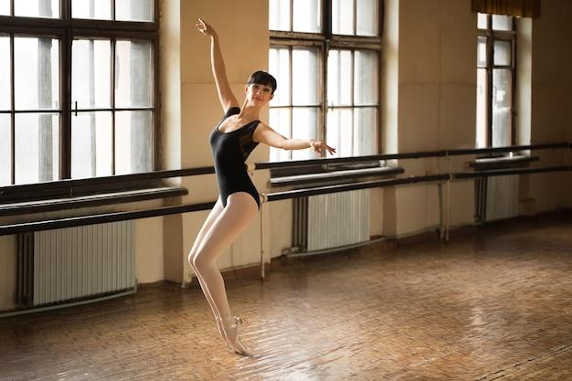 ライトホールの大きな窓の近くの黒い練習バレエの位置にある優雅なバレリーナ