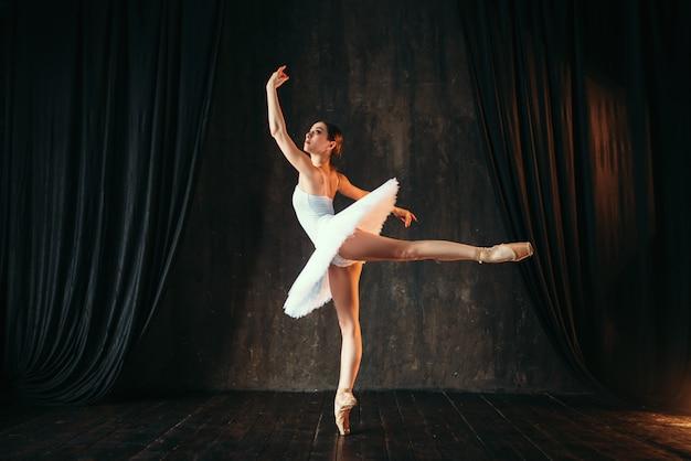 Изящная балерина в белом платье танцует в классе. тренировка артиста балета на сцене