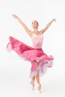 Graceful ballerina in pink tutu posing against white background