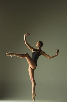 灰色のスタジオの背景に分離された優雅なバレエダンサーまたは古典的なバレリーナダンス。柔軟性と優雅さを示しています。ダンス、アーティスト、コンテンポラリー、ムーブメント、アクション、モーションのコンセプト。