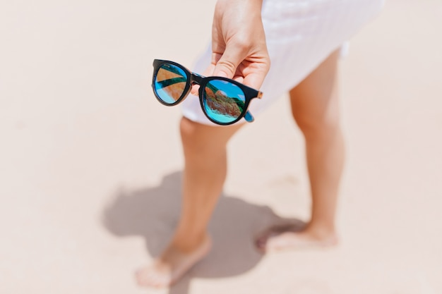 Изящная босая дама позирует в солнечных очках. открытый портрет женщины с загорелыми ногами в стеклах блеска на переднем плане.