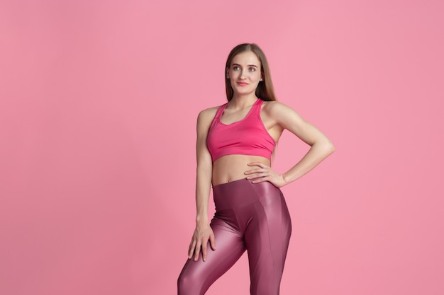 Graceful. beautiful young female athlete practicing , monochrome pink portrait. sportive fit caucasian model posing. body building, healthy lifestyle, beauty and action concept.