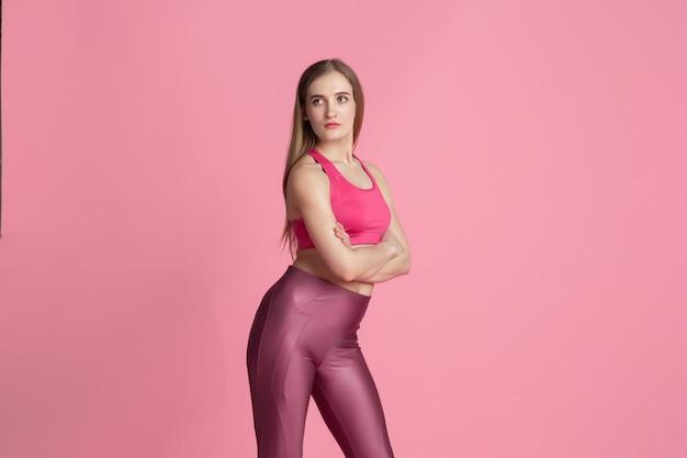 優雅。練習中の美しい若い女性アスリート、モノクロのピンクの肖像画。スポーティーフィットの白人モデルのポーズ。ボディービル、健康的なライフスタイル、美しさとアクションのコンセプト。