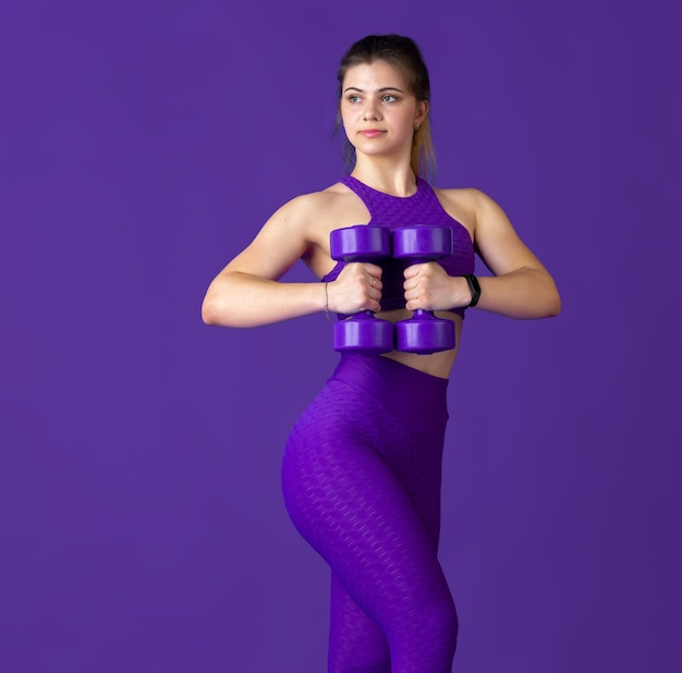 Graceful. beautiful young female athlete practicing in studio, monochrome purple portrait.