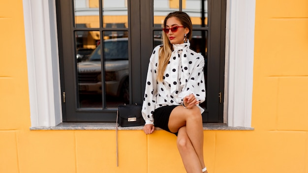 Graceful blond lady in white blouse and black skirt standing on yellow.
