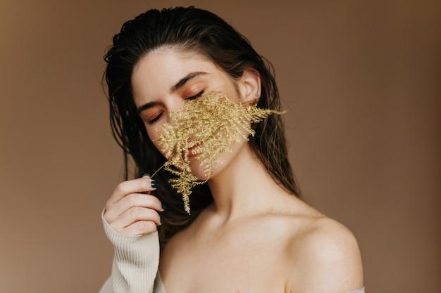 Graziosa ragazza bruna in posa con la foglia verde. felice donna caucasica in piedi sul muro marrone con pianta.