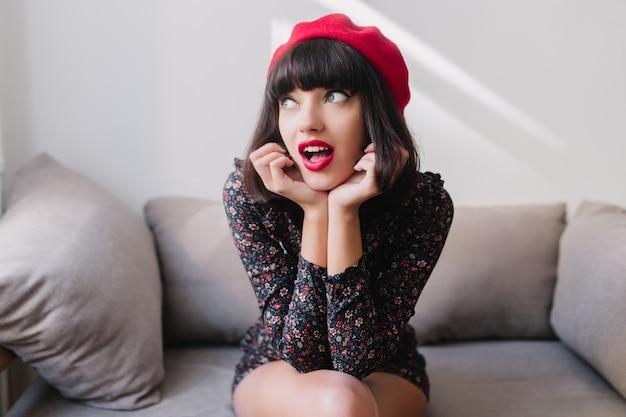 Graziosa ragazza bruna in berretto francese alla moda e abito vintage ha ricordato qualcosa di importante. ritratto di affascinante giovane donna che indossa un taglio di capelli corto, seduto sul divano con l'espressione del viso divertente