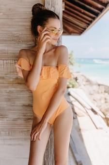 木製の壁に目をそらしているスタイリッシュな水着の優雅な白人の女の子。リゾートで黄色いサングラスでポーズをとっているスリムな日焼けした女性モデルの写真。