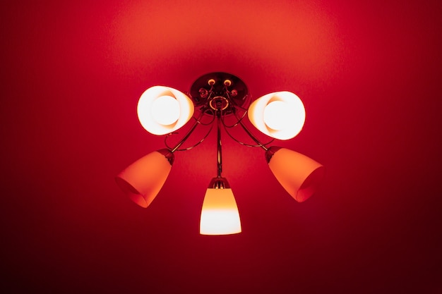 Graceful chandelier with five arms hangs from the ceiling, red festive background.