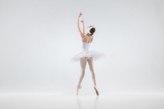 白いスタジオの背景に分離された優雅な古典的なバレリーナダンス。白鳥のキャラクターのような優しい服を着た女性。優雅さ、芸術家、動き、行動、動きの概念。無重力に見えます。
