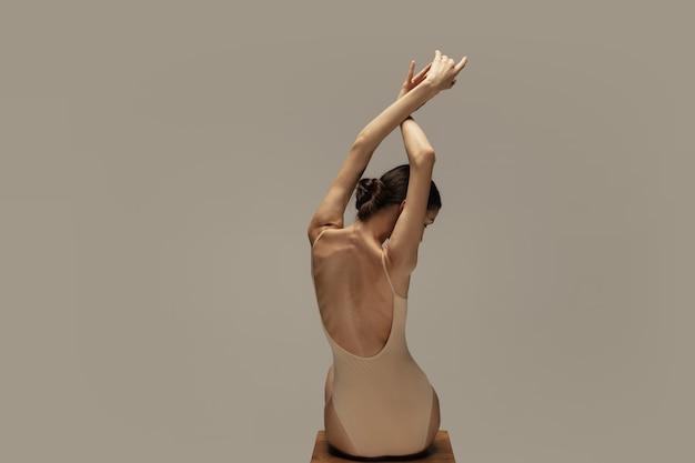 パステルブラウンのスタジオの背景に分離されたポーズで、優雅な古典的なバレリーナダンス。女性の背中と手。優雅さ、芸術家、動き、行動、動きの概念。無重力で柔軟に見えます。