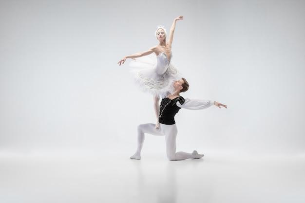 Ballerini di balletto classico grazioso che ballano coppia in vestiti bianchi teneri come caratteri di un cigno bianco. la grazia, l'artista, il movimento, l'azione e il concetto di movimento.