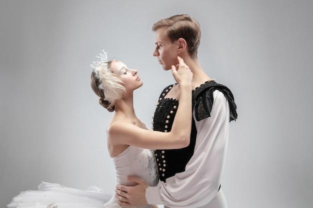 白い背景に分離して踊る優雅なクラシックバレエダンサー。