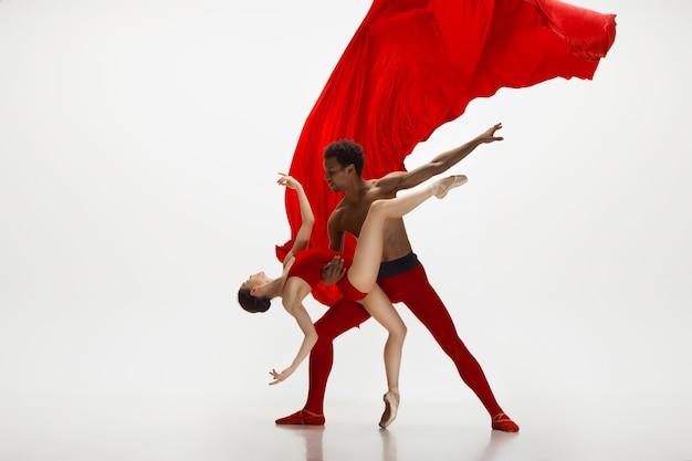 Изящные классические танцоры балета танцуют на белом фоне студии. паре в ярко-красных одеждах нравится сочетание вина и молока. изящество, художник, движение, действие и концепция движения.