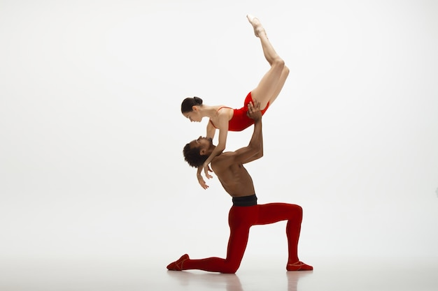 Graceful classic ballet dancers dancing isolated on white studio background. couple in bright red clothes like a combination of wine and milk. the grace, artist, movement, action and motion concept.