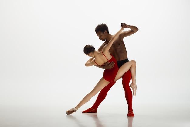 Ballerini di balletto classico graziosi che ballano isolati sulla parete bianca. la grazia, l'artista, il movimento, l'azione e il concetto di movimento.
