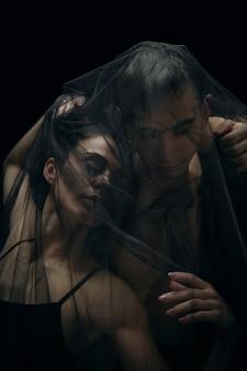 黒のスタジオの背景に分離された優雅なクラシックバレエダンサー。