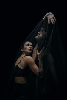 검은 스튜디오 배경에 고립 된 우아한 클래식 발레 댄서