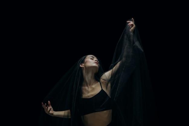 黒のスタジオの背景に分離された優雅な古典的な女性のバレエダンサー