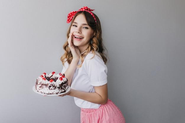 ストロベリーパイで何かを祝う優雅な巻き毛の白人女性。ケーキでポーズをとって華やかな誕生日の女の子の肖像画。