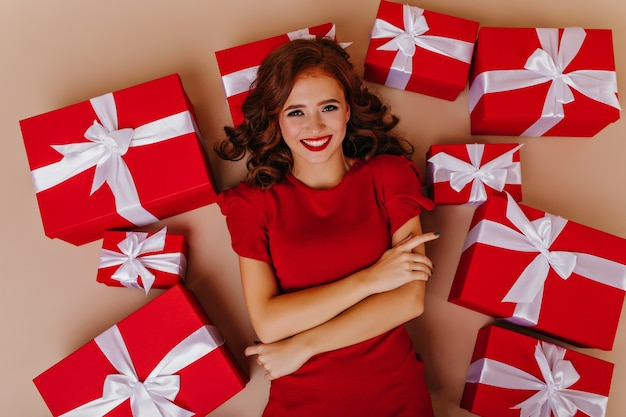 Graceful curly woman in good mood posing on the floor with gifts. attractive female model enjoying christmas party.