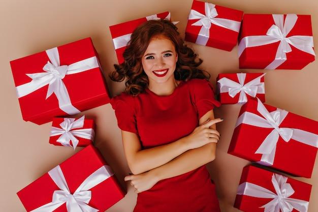 선물과 함께 바닥에 포즈 좋은 분위기에서 우아한 곱슬 여자. 크리스마스 파티를 즐기는 매력적인 여성 모델.