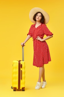 Graceful curly woman in red dress and hat with suitcase going traveling on yellow background.