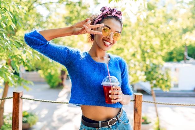 Изящная милая девочка, показывающая знаки руками и держащая вкусный лимонад.