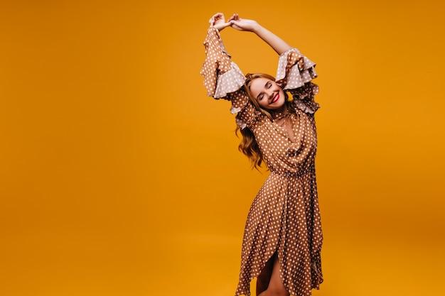 Изящная милая женщина в винтажном платье, улыбаясь с закрытыми глазами. внутренний портрет великолепной белой модели со светлыми волосами.