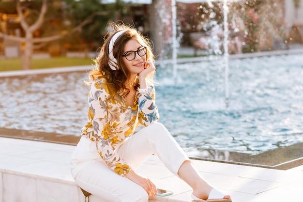 Изящная темноволосая девушка в модных белых штанах отдыхает в парке у красивого фонтана с игривой улыбкой